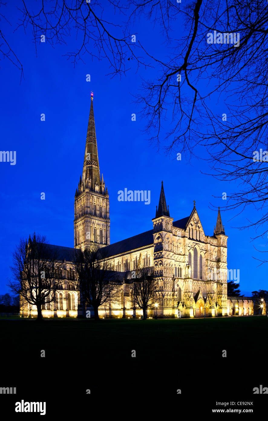 The floodlit west front and spire of medieval Salisbury Cathedral, Wiltshire, England, UK at twilight. - Stock Image