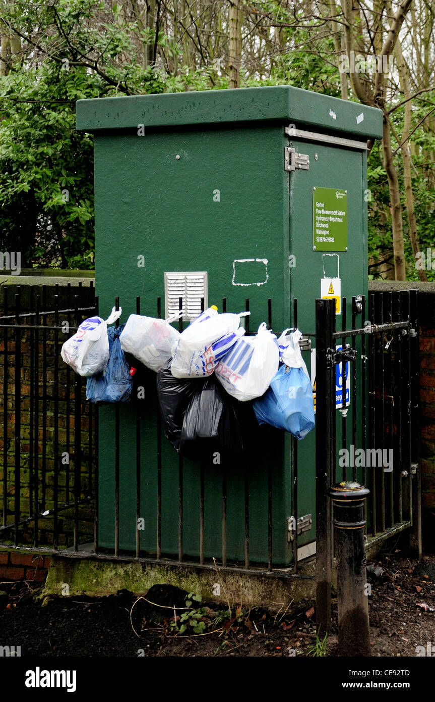 Flow measurement station in Gorton, Manchester with plastic bags of rubbish tied to barrier fence - Stock Image