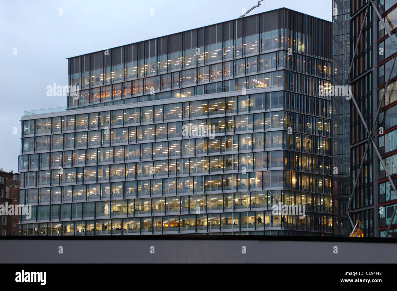 Disappearing Glass Office Buildings In The Morning Wide: Lit Up Office Building With Large Glass Windows In The