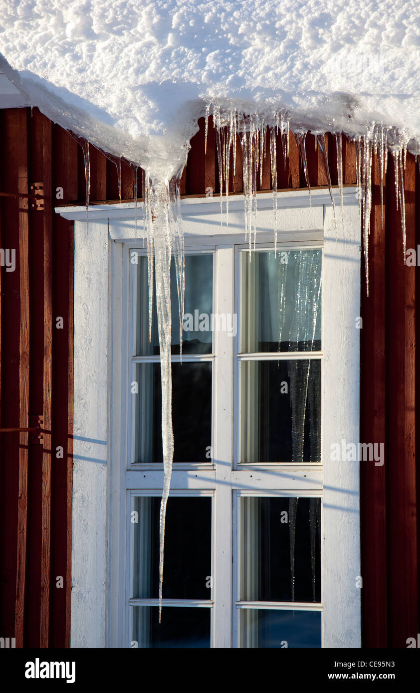 Icicles hanging from house eaves , Finland Stock Photo