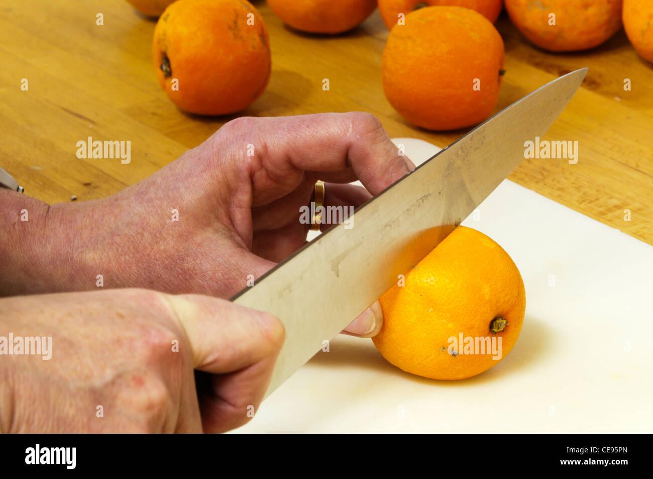 Slicing Oranges to make Marmalade. - Stock Image