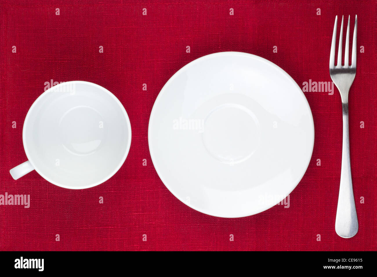 White kitchen utensils (cup, plate, fork) on red background Stock Photo