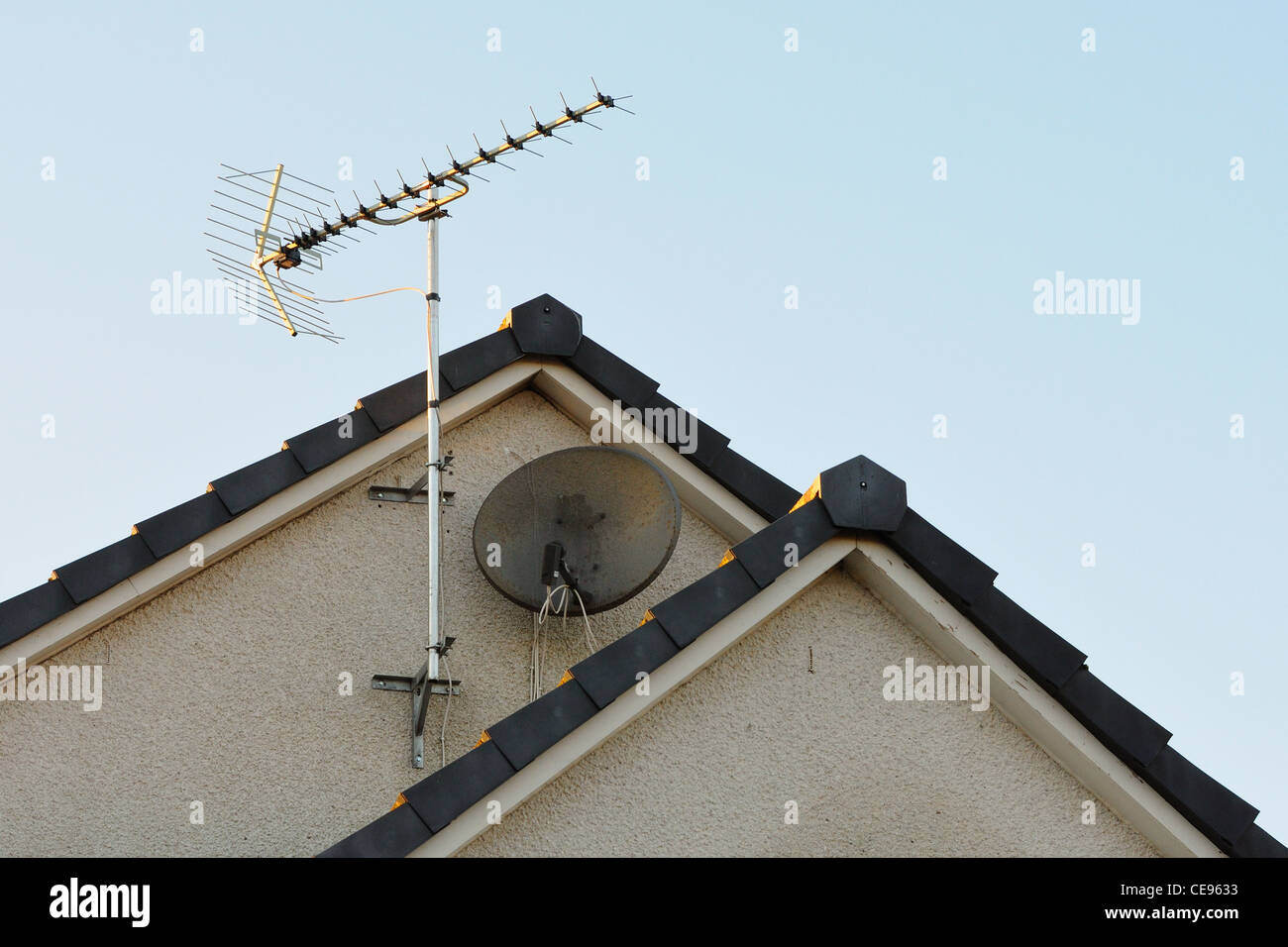 TV aerial and satellite dish on gable wall of modern house. - Stock Image