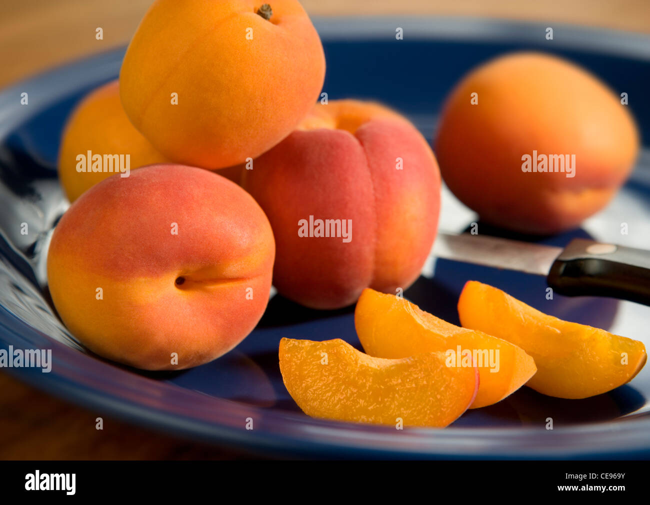 Whole and sliced apricots on a blue ceramic plate. - Stock Image