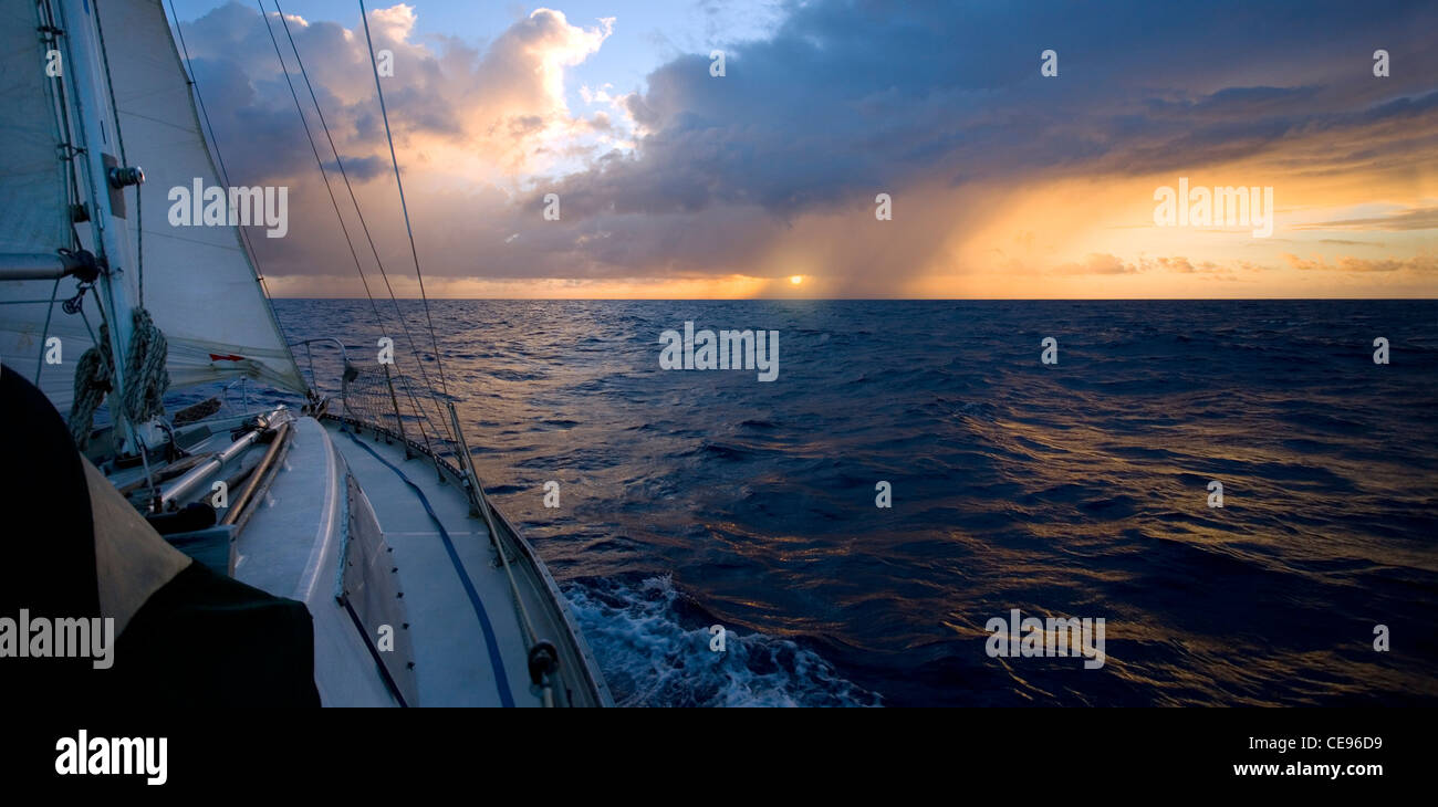 A sailboat on an ocean passage heads toward the sun and a small rain squall. - Stock Image