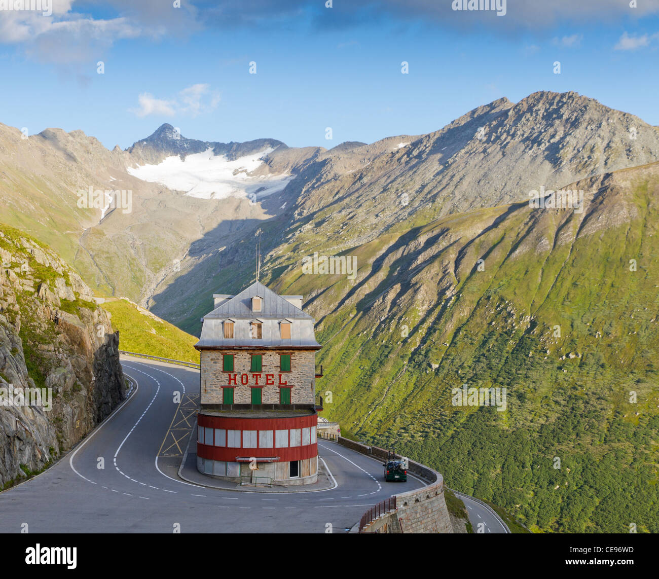 lonely, vintage hotel at Furka pass, set in barren alpine mountains in pass road bend - Stock Image