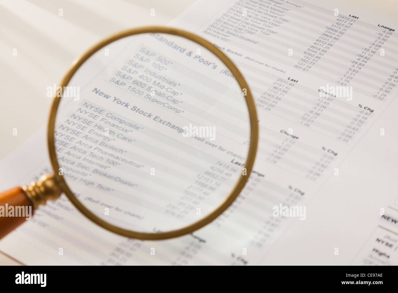 Studio shot of magnifying glass over financial pages - Stock Image