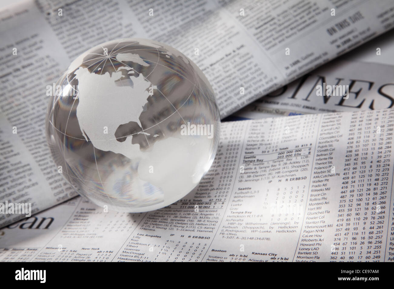 Studio shot of globe on financial pages - Stock Image