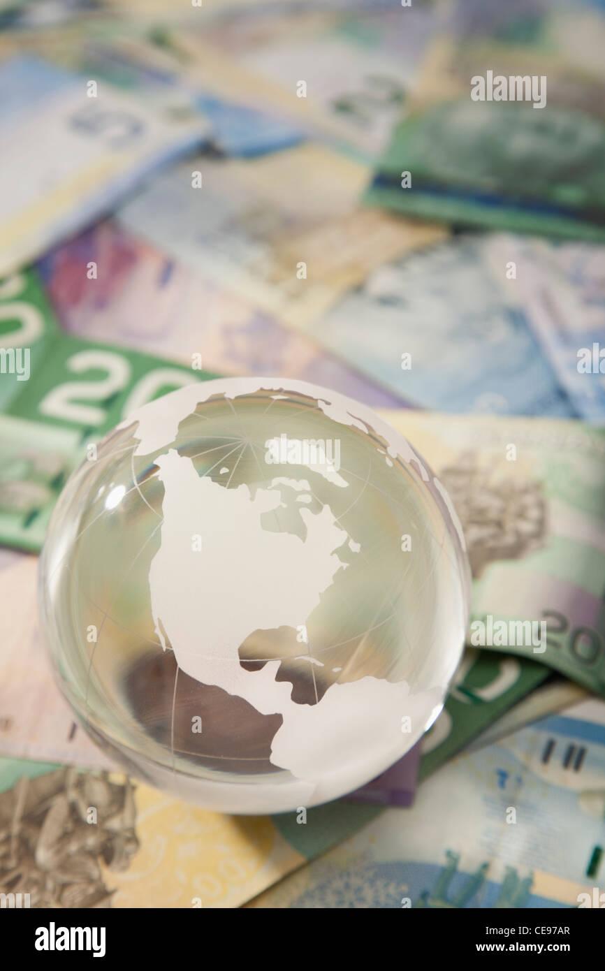 Studio shot of globe on banknotes - Stock Image