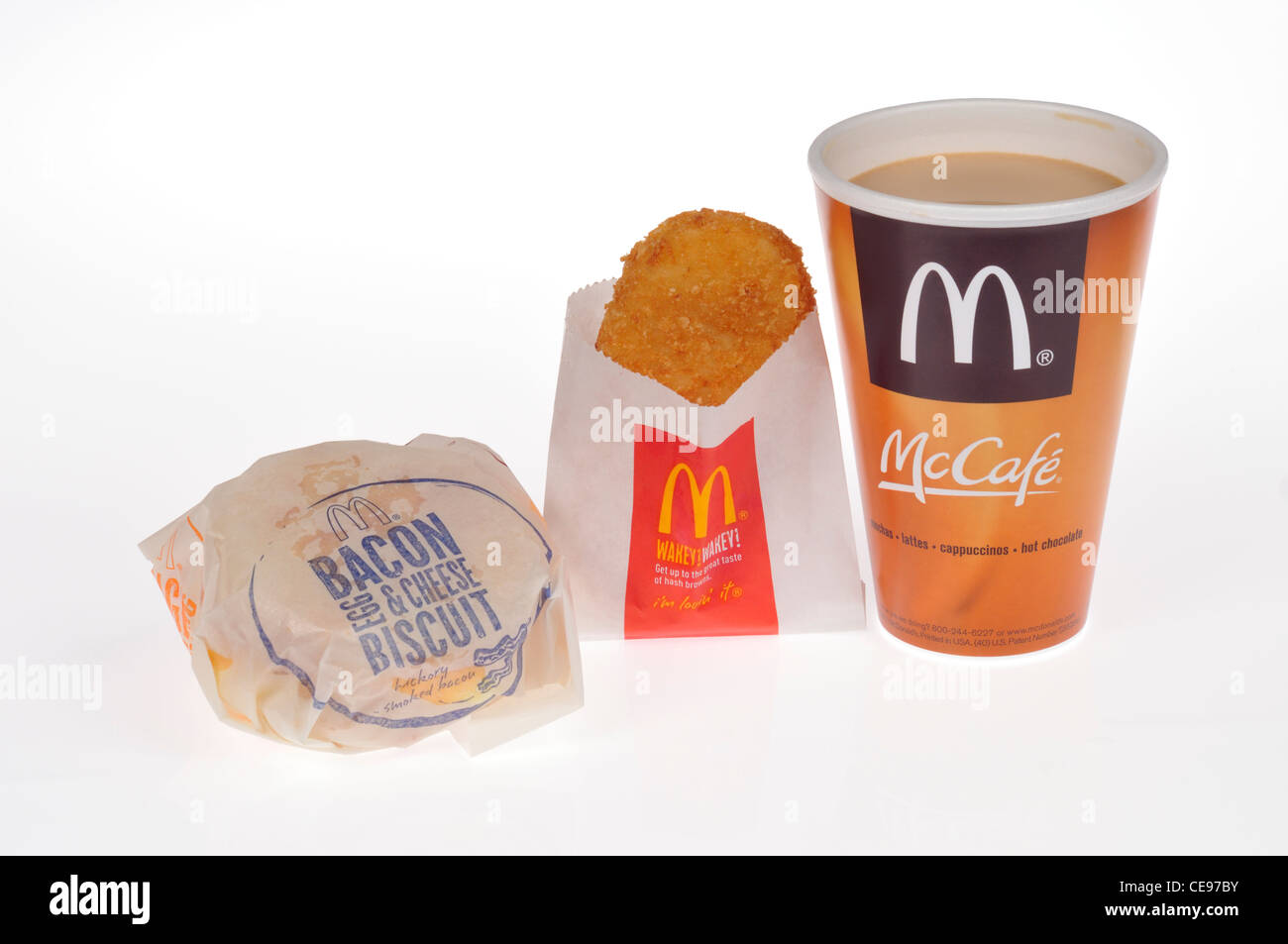 McDonalds breakfast of bacon egg and cheese biscuit, hash brown potato and McCafe hot coffee on white background - Stock Image