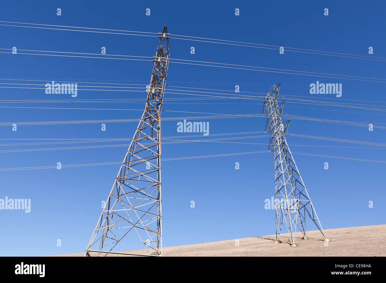 Electricity pylons against blue sky - California, USA - Stock Image