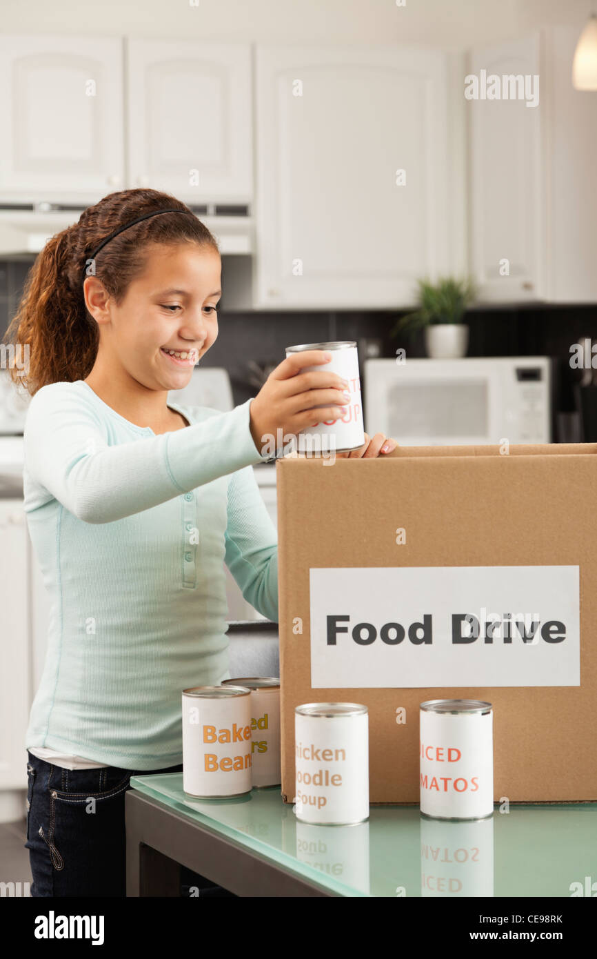 USA, Illinois, Metamora, Smiling girl (10-11) putting canned food into cardboard box in kitchen - Stock Image