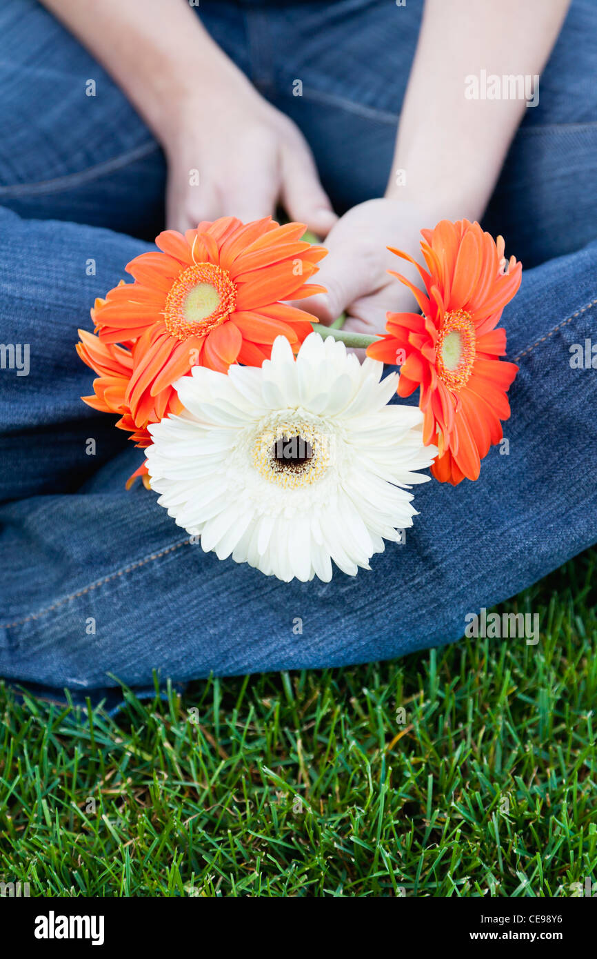 USA, Illinois, Metamora, Close-up of young woman sitting on grass, holding flowers - Stock Image