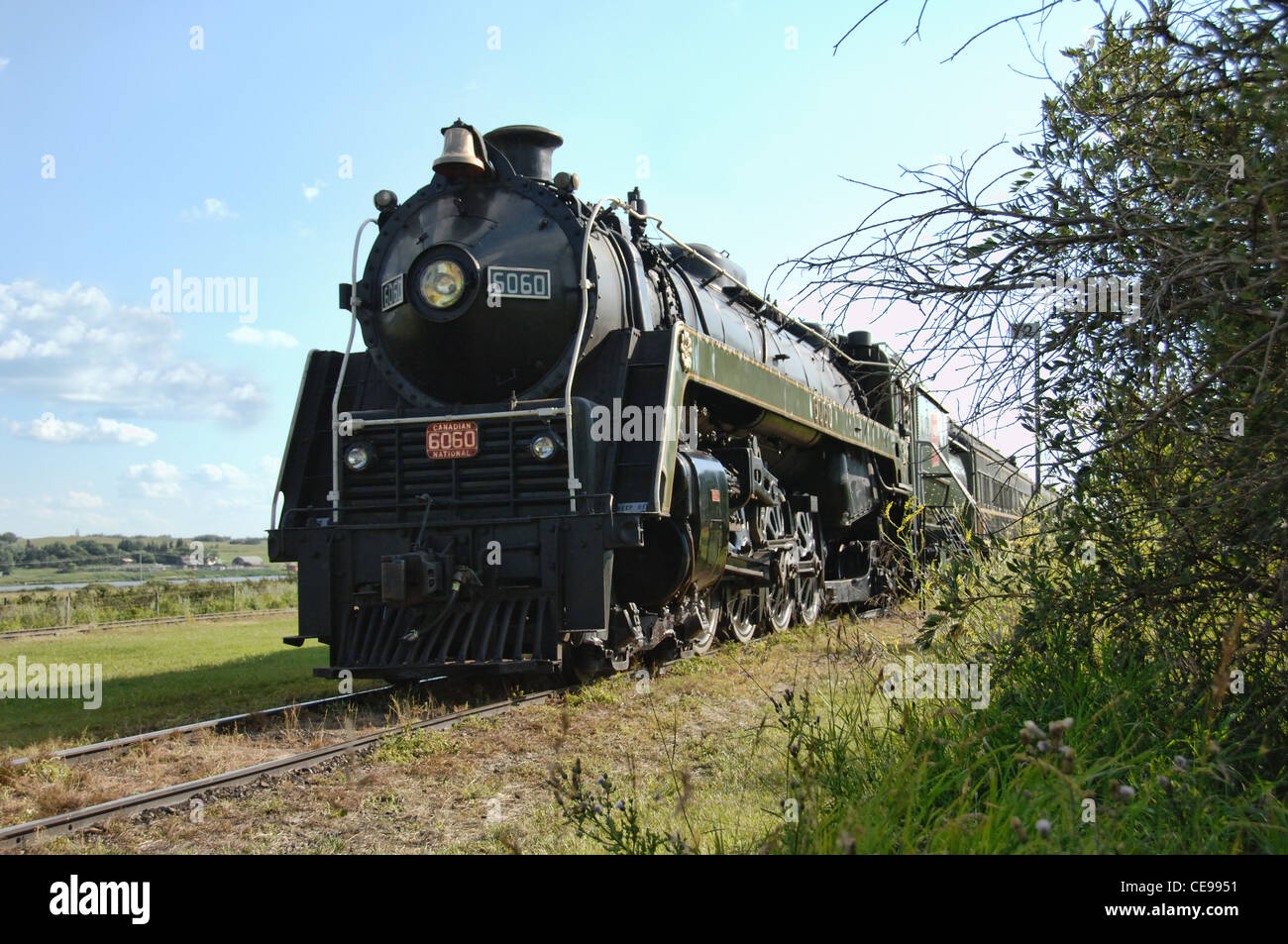An old steam locomotive stopped on railway tracks. Stock Photo