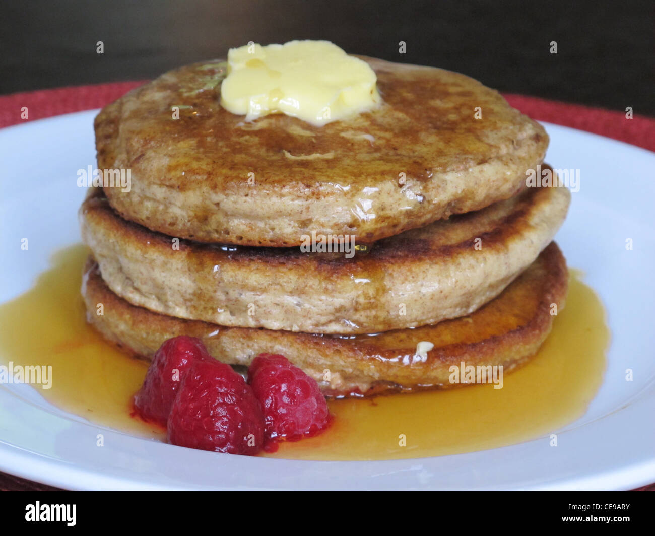A delicious pancake with maple syrup and butter, with raspberries on the side.  Breakfast food which has high caloric - Stock Image