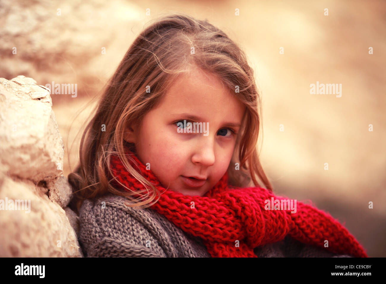 little sweetie girl child in a red scarf - Stock Image