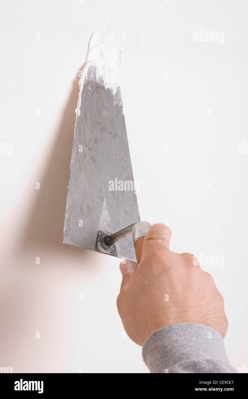 Putty Knife with Paste to Repair Wall Damage - Stock Image