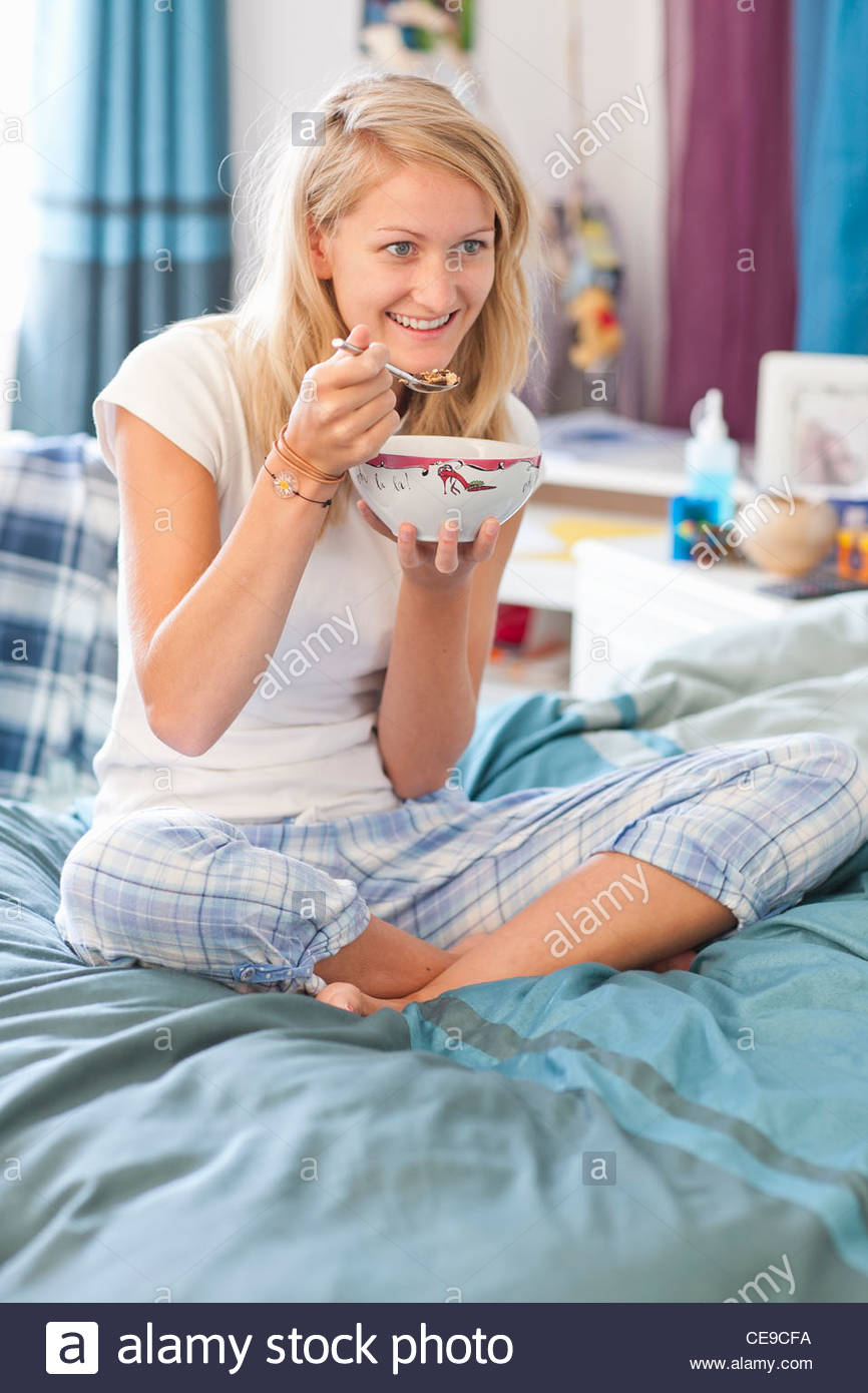117c4cae3cd1c7 Smiling young woman in pajamas eating cereal in bed - Stock Image