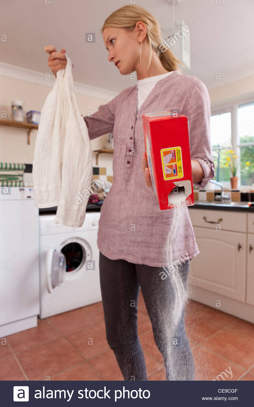 Young woman holding shirt and spilling detergent in laundry room - Stock Image