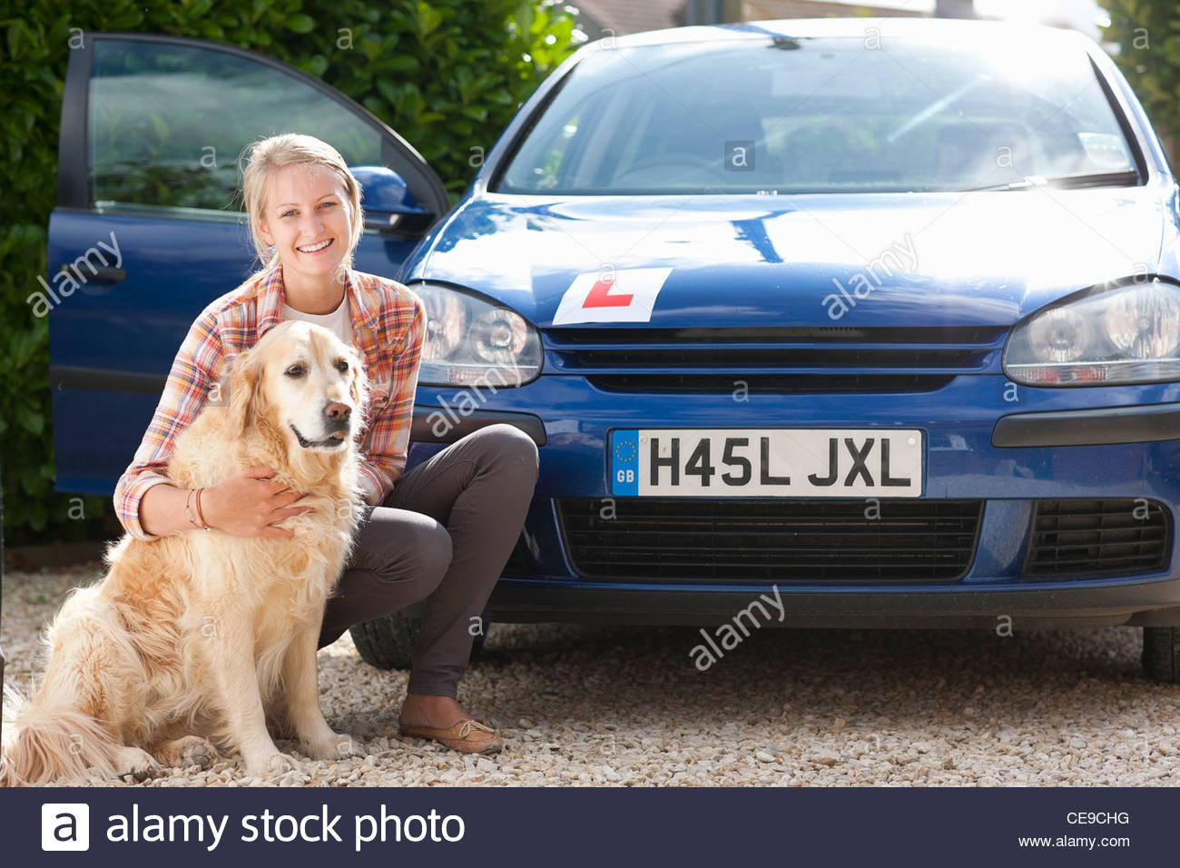 Portrait of smiling young woman with dog in front of car with learner's permit - Stock Image