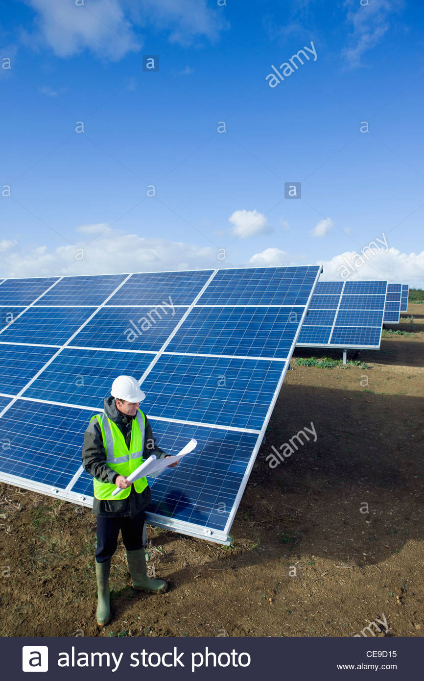 Engineer with blueprint standing next to solar panels - Stock Image