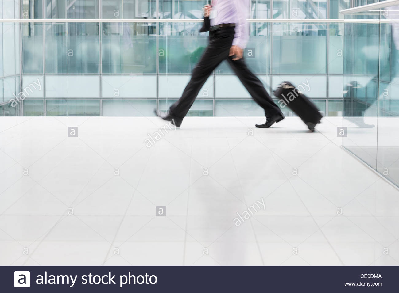 Businessman pulling suitcase in airport - Stock Image