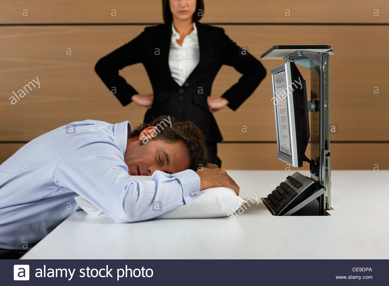 Angry businesswoman looking down at businessman sleeping on pillow at desk - Stock Image