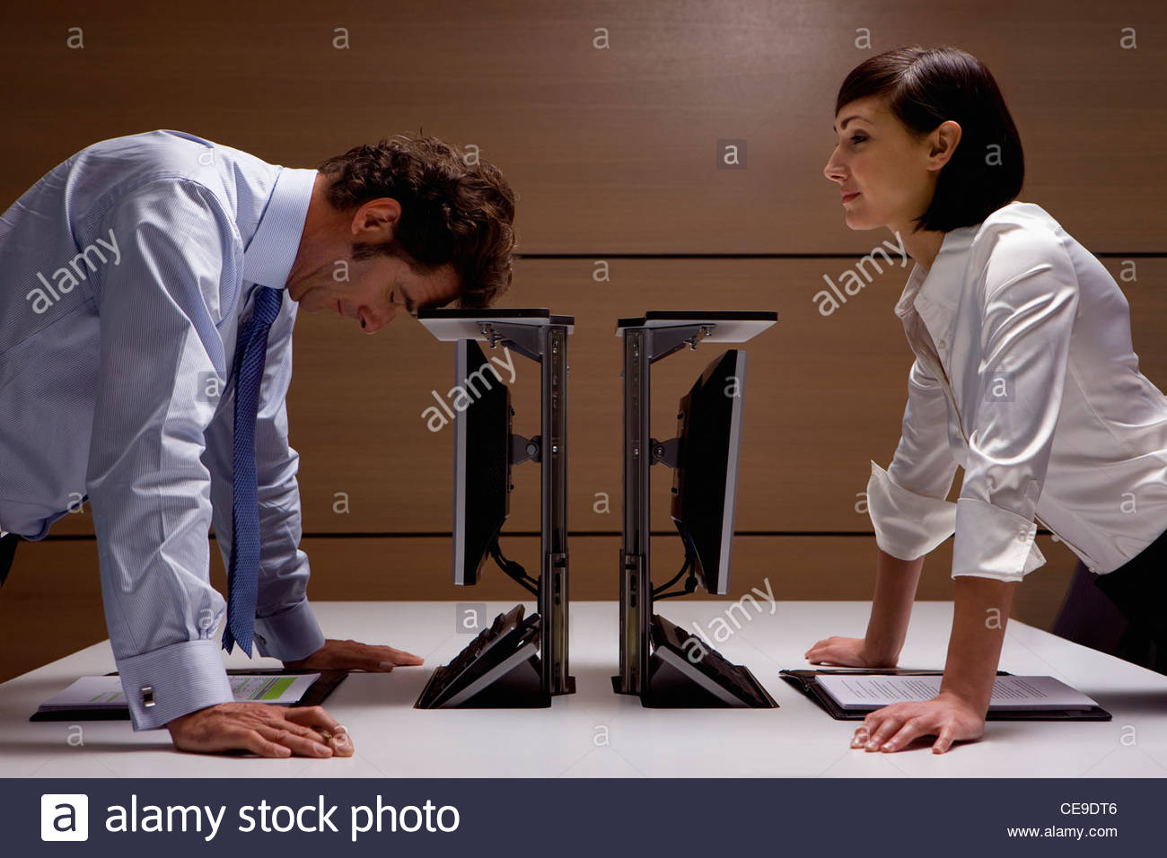 Businesswoman watching businessman lean on computer in office - Stock Image