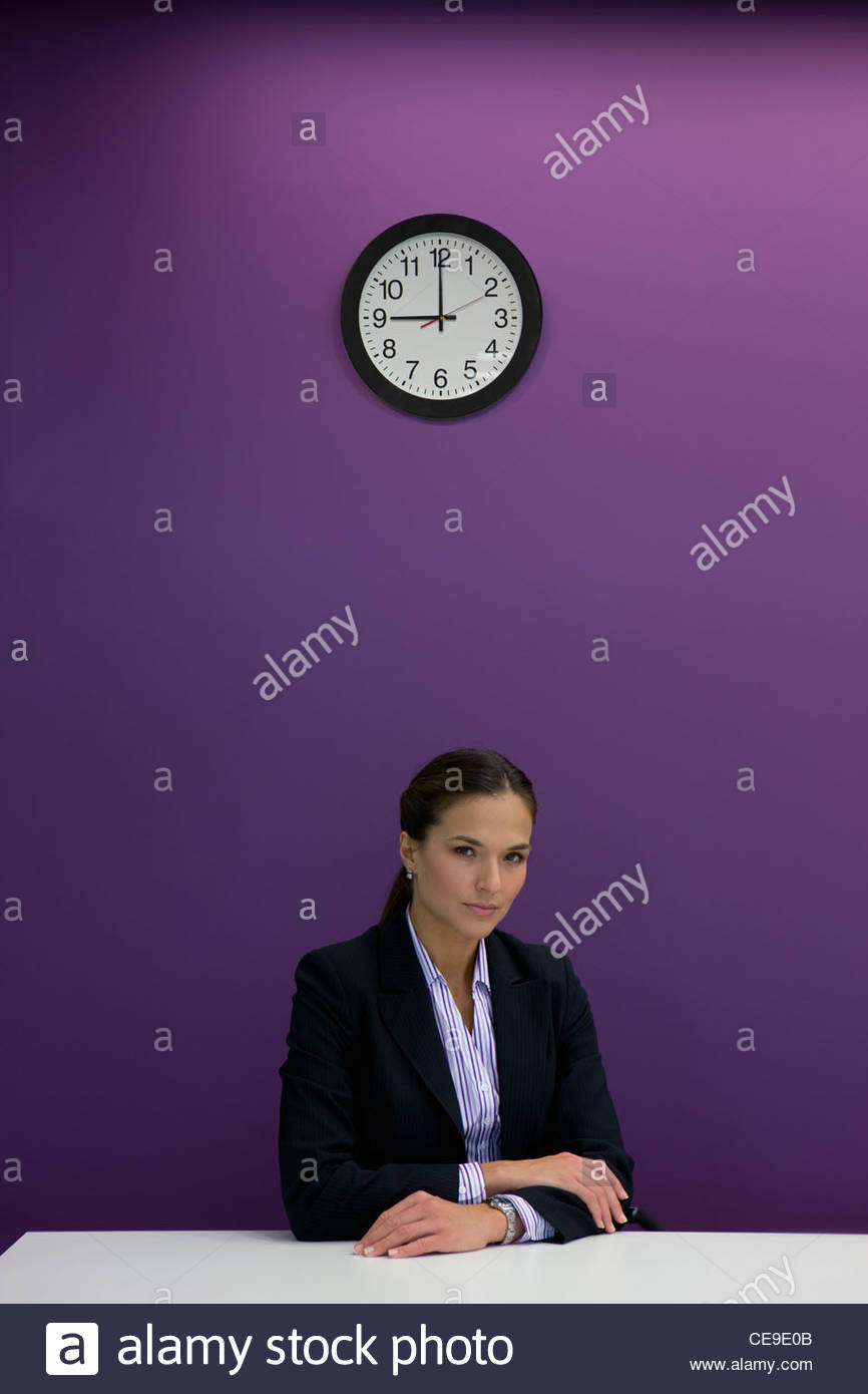 Portrait of serious businesswoman sitting at desk under clock - Stock Image