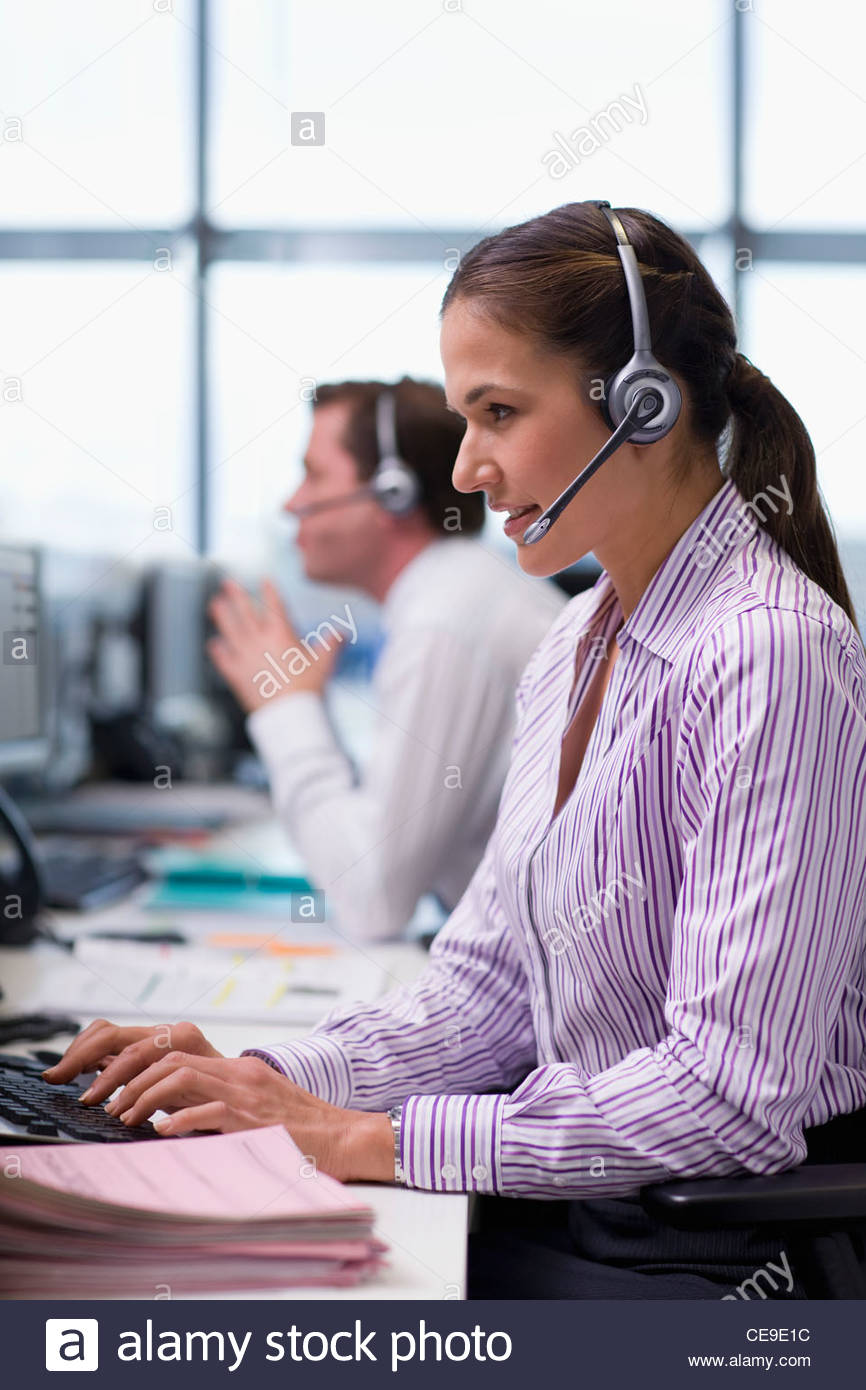Businesswoman wearing headset and typing on computer keyboard in office - Stock Image
