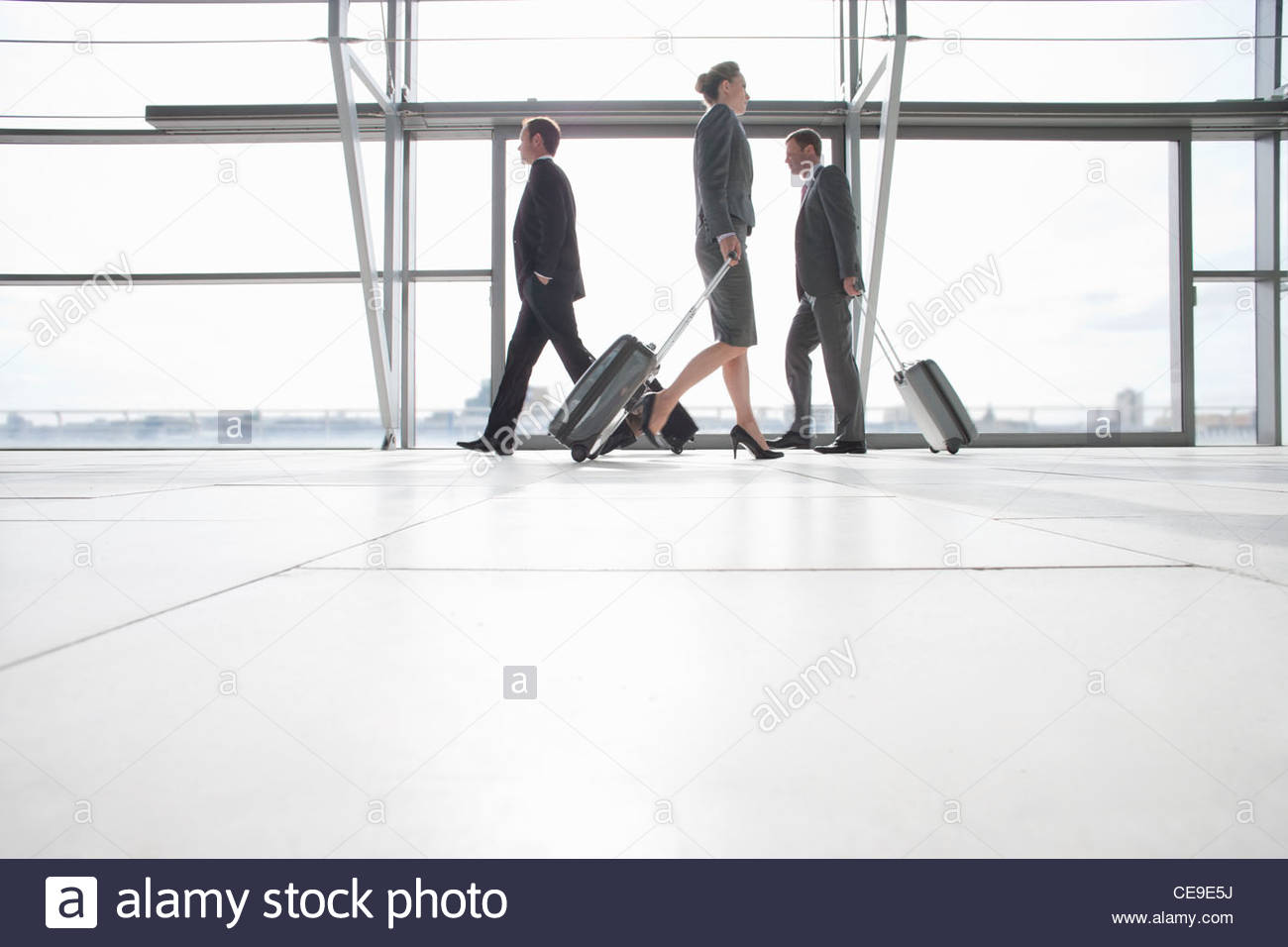 Business people pulling suitcases in airport - Stock Image