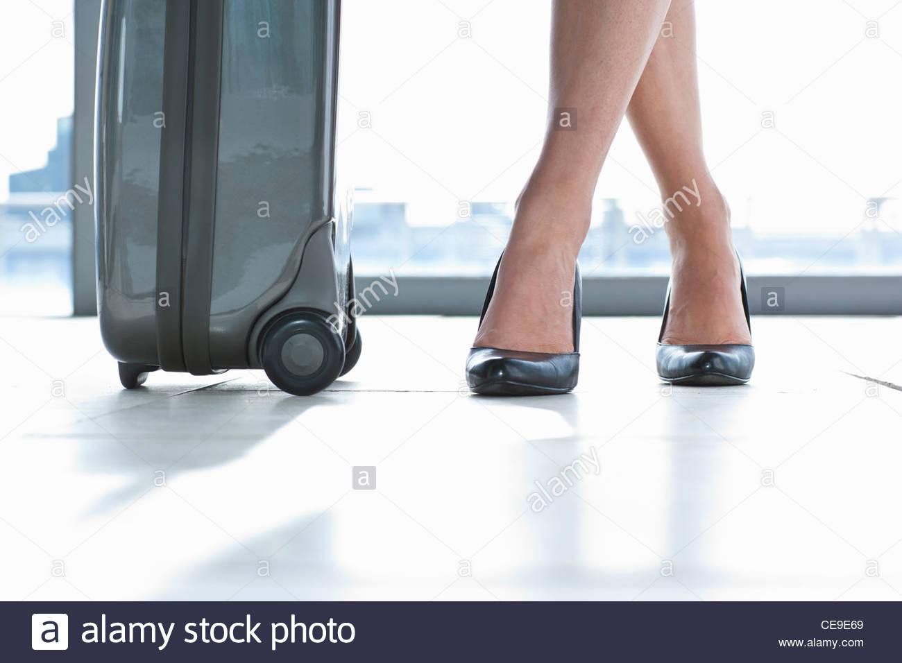 Close up of suitcase and businesswoman's high heels - Stock Image