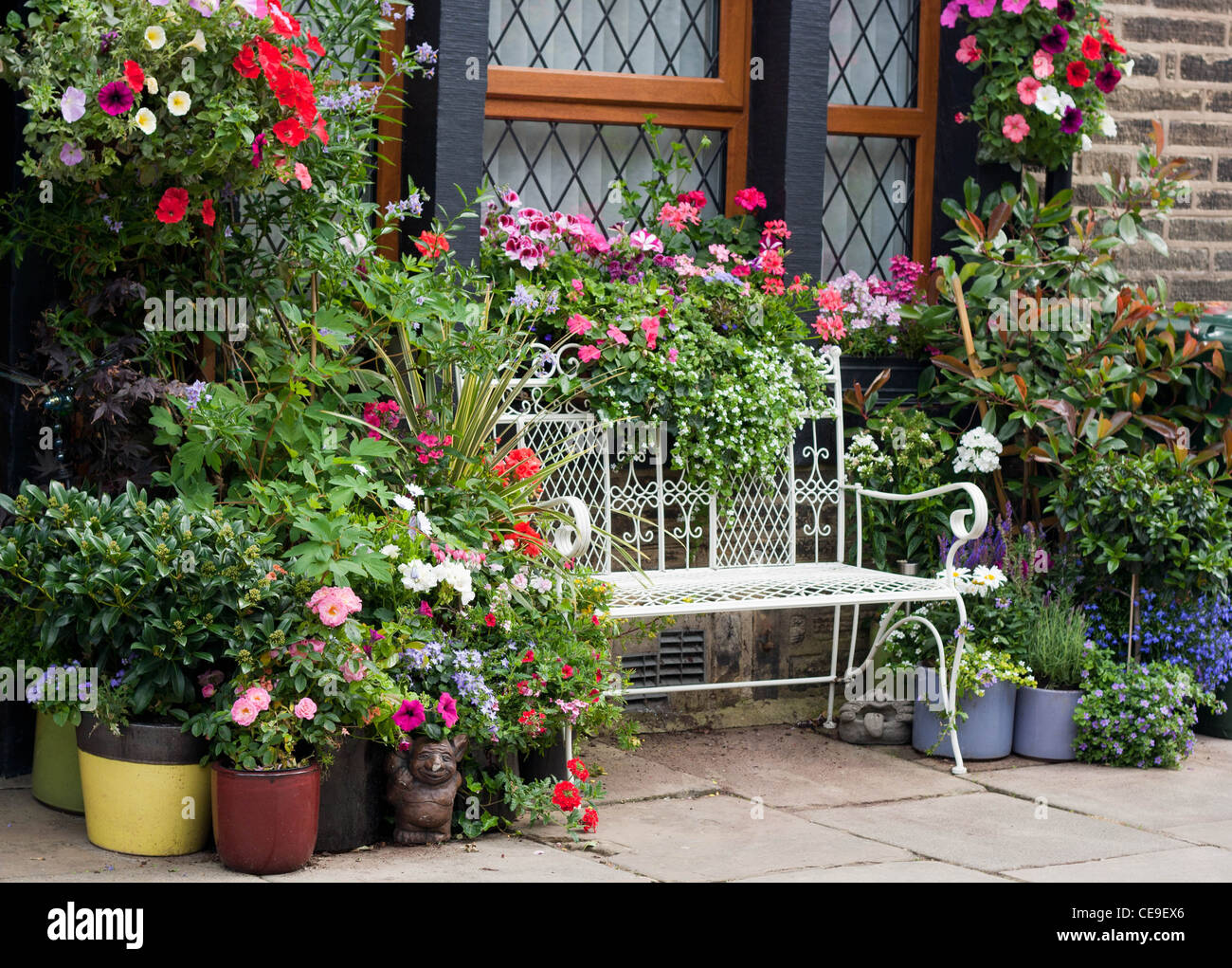 Beautiful white wire bench among flowers Stock Photo