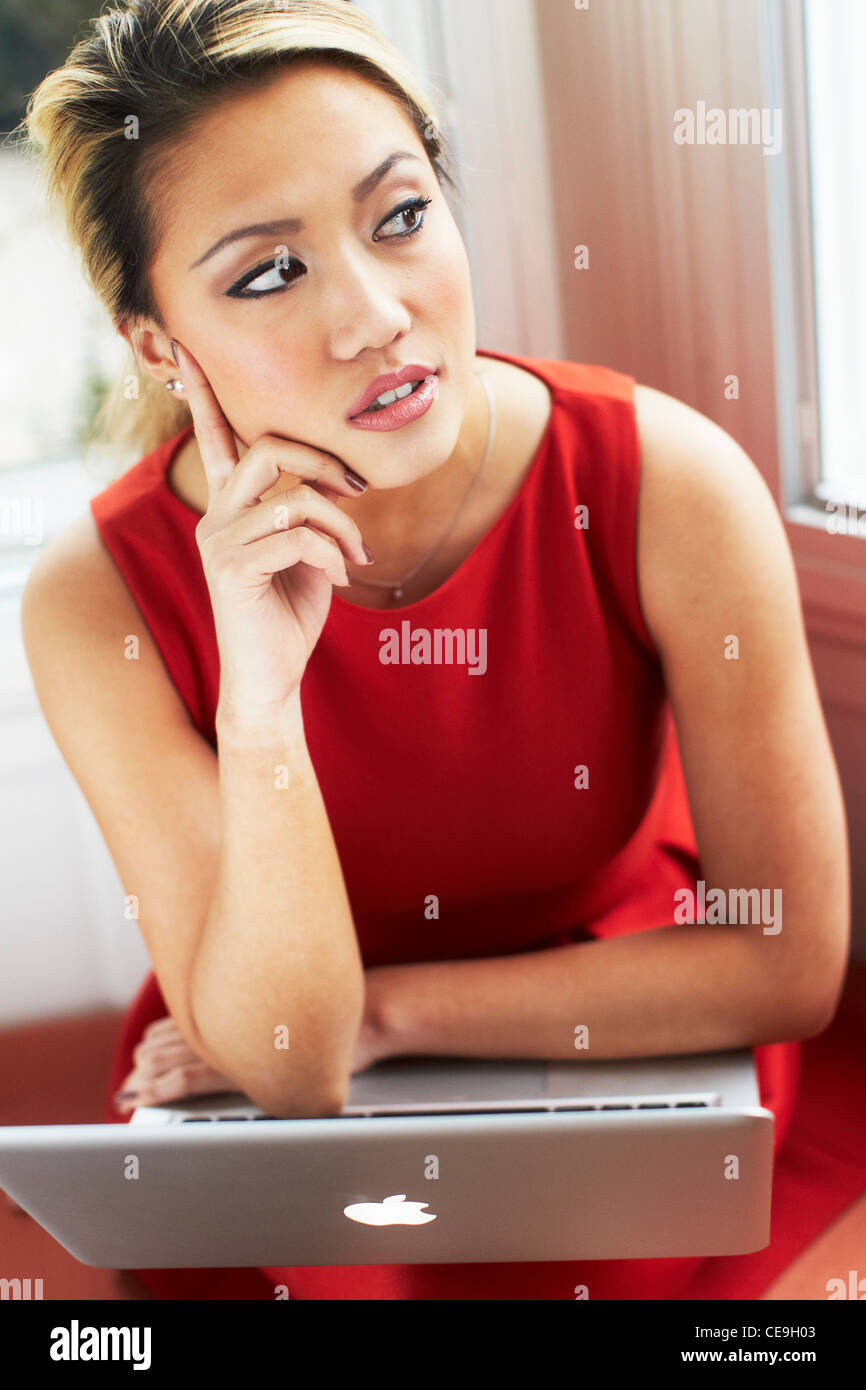 Woman looking concerned using laptop - Stock Image