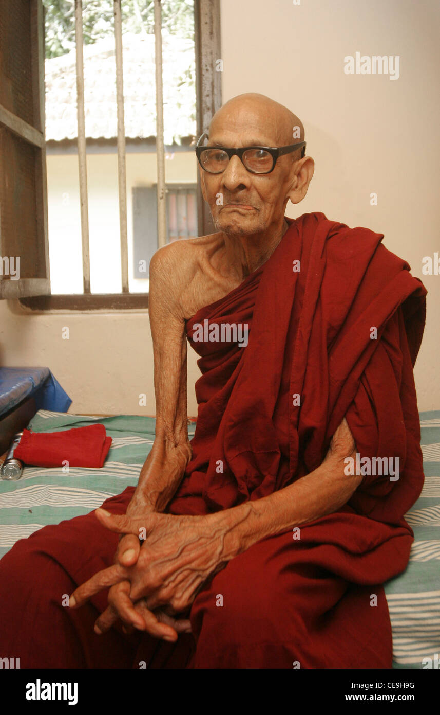 A elderly Buddhist Monk sits on the side of his bed in his room at a temple in South West Sri Lanka Stock Photo