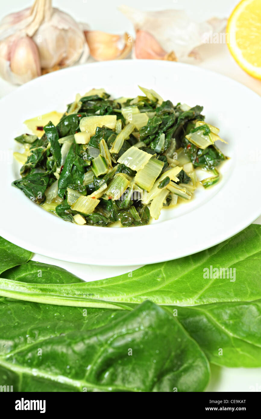 A side dish of swiss chard cooked in olive oil with garlic and chilli flakes and then tossed in lemon juice, with - Stock Image