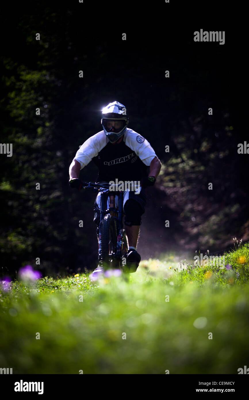 Mountainbiker riding fast on mountain trail in Lauterbrunnen, Switzerland - Stock Image