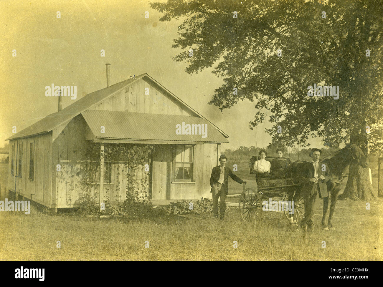 Settlers in front of wooden home on homestead during the late 1800s with horse and buggy carriage - Stock Image