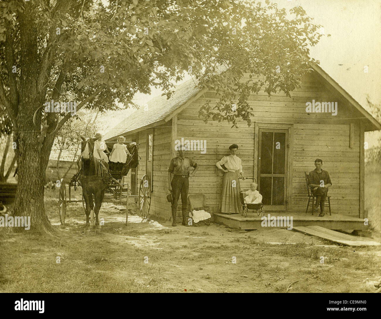 Homesteaders with horse and buggy standing in front of wooden house in 1916 Illinois pioneers farmers midwest homestead - Stock Image
