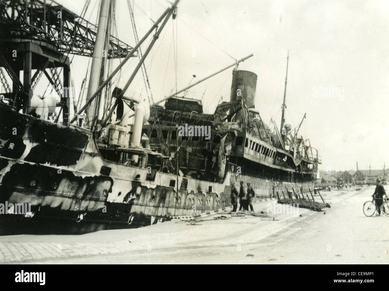 destroyed ship with Nazi German soldiers standing next during WWII european theater - Stock Image