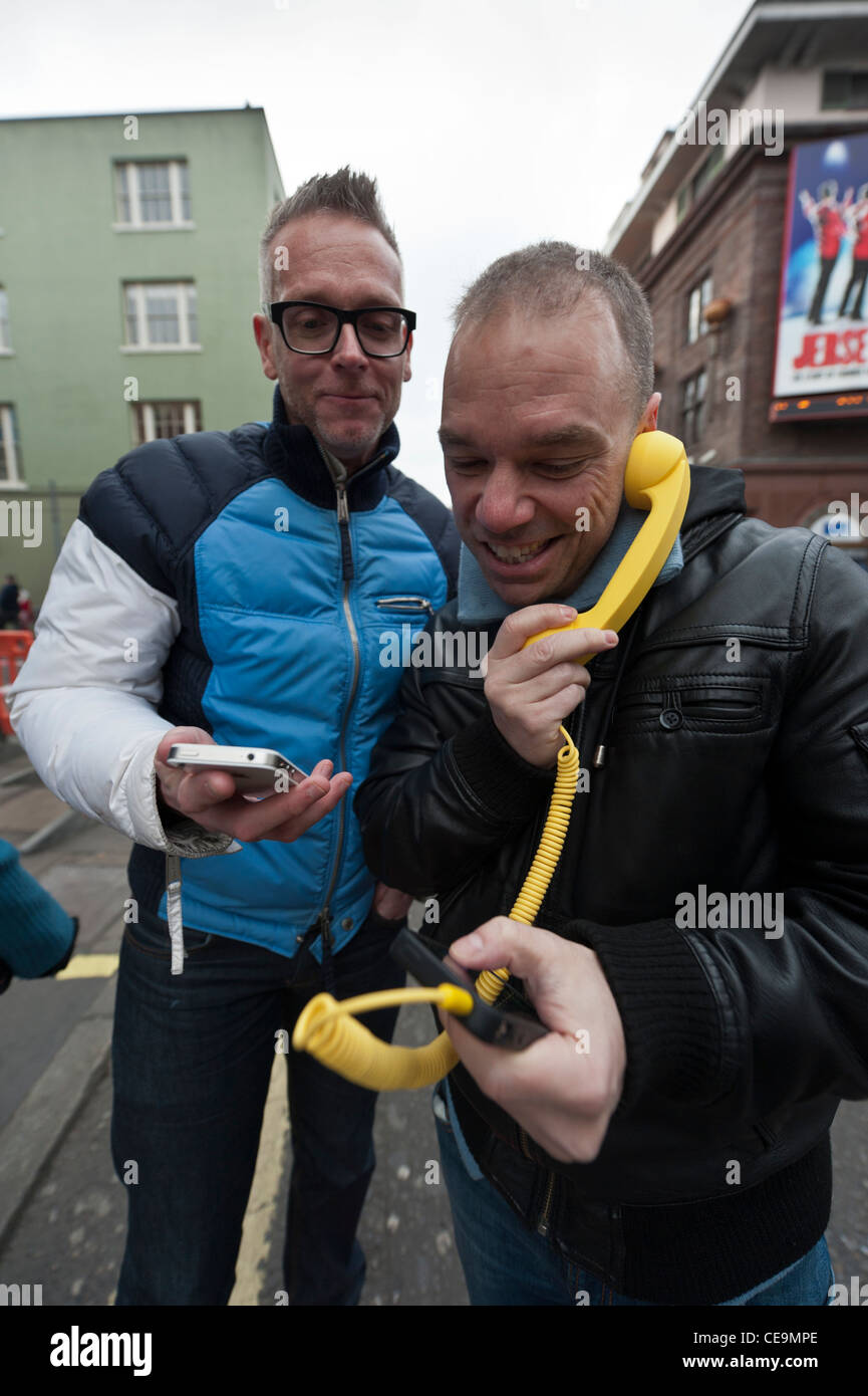 Two men using a comical iphone telephone handset on a street in London - Stock Image