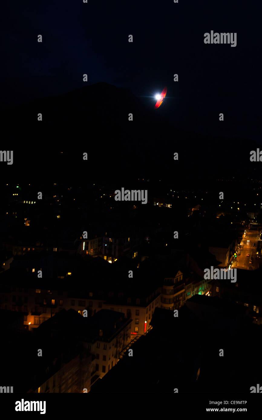 Acro paraglider pilot performing tricks at night over Interlaken illuminated by flash, Switzerland - Stock Image