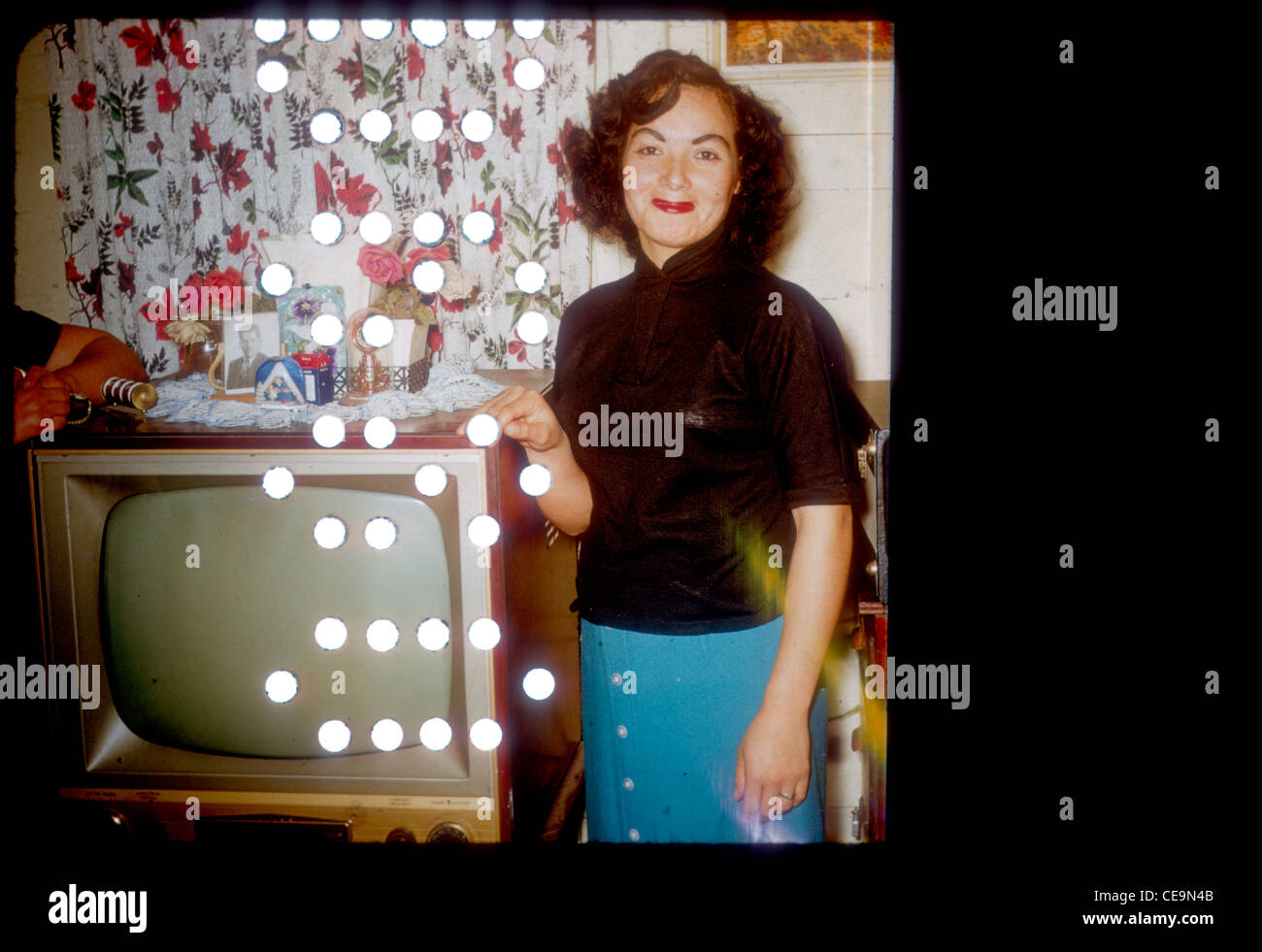 Fasionable mexican american woman standing next to television during the early 1960s. tv television latino - Stock Image