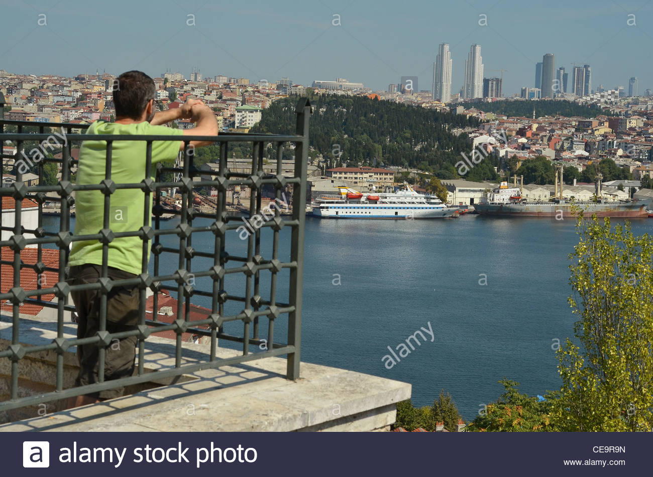 A man looks at the Golden Horn and the skyscrapers of the Levent business district from a vantage point in Fatih, - Stock Image