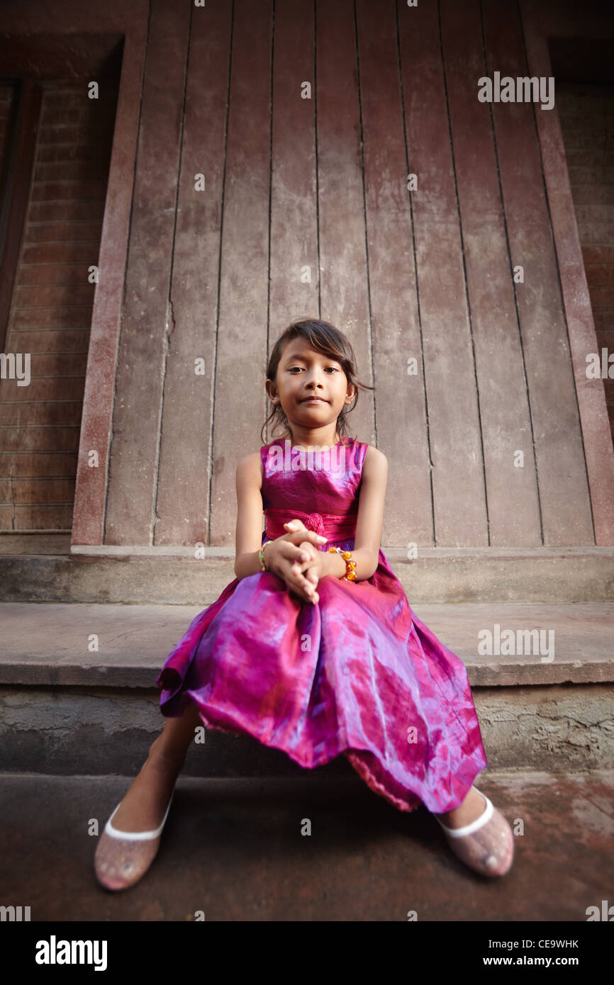 Portrait of cute Asian female child in pink dress looking at camera - Stock Image