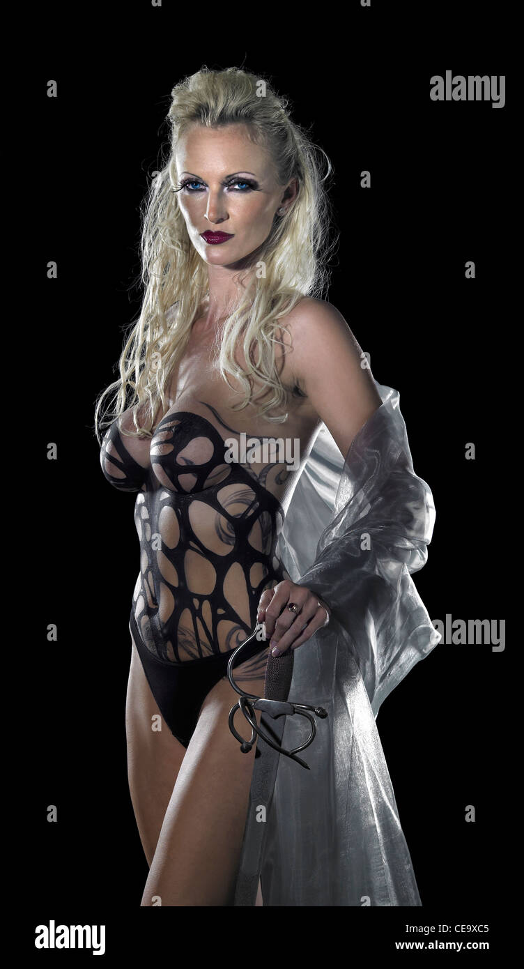 bodypainted blond woman posing in dark back - Stock Image