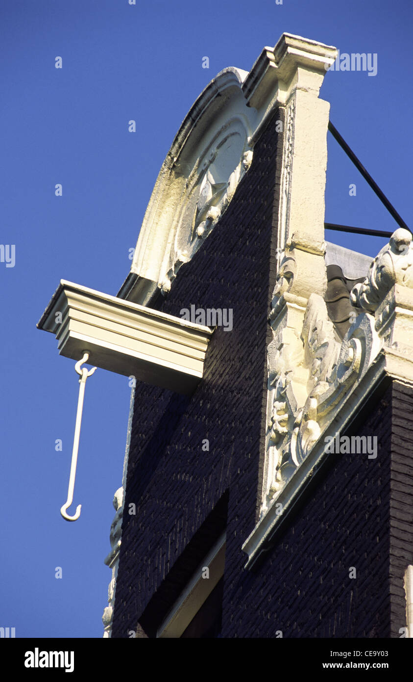 Hooks and beams are used for hoisting furniture on old Dutch buildings. Amsterdam, Holland. - Stock Image