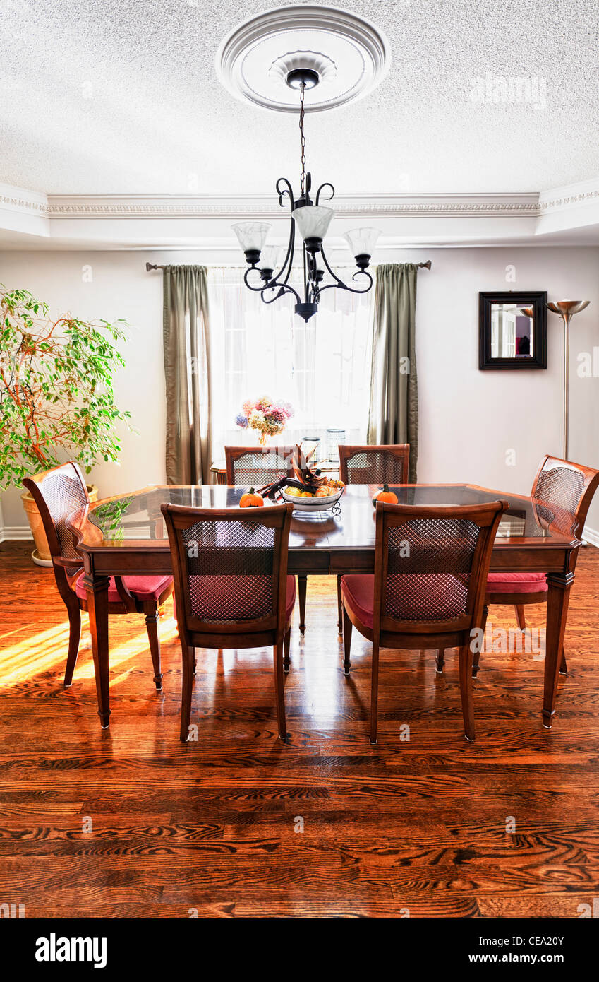 Dining room interior with wooden table and chairs in house - Stock Image