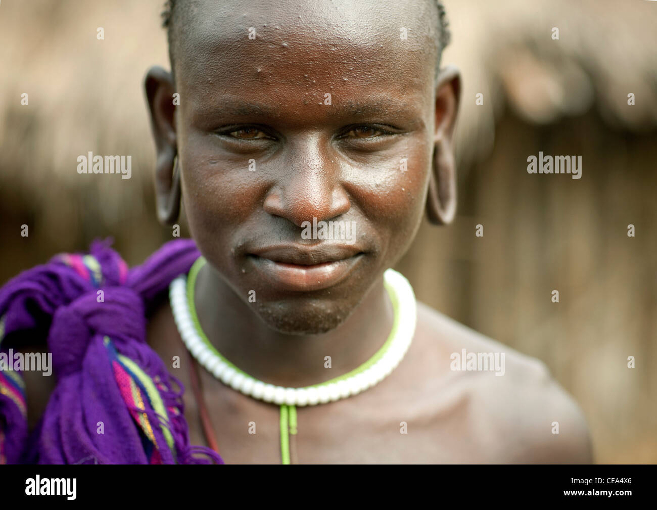 Young Surma Woman With Extended Ear Lobes Tricky Look Ethiopia - Stock Image