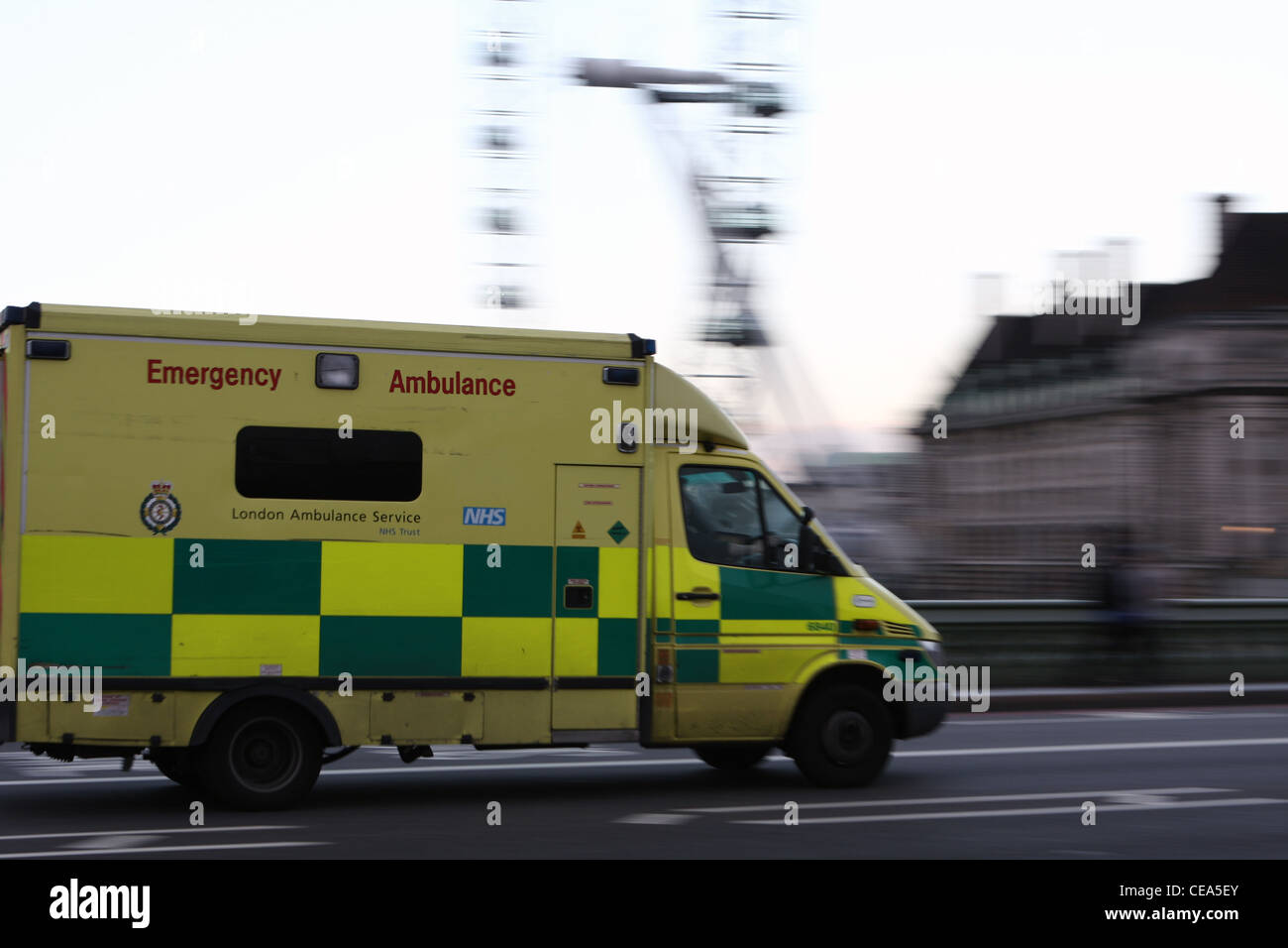 An ambulance speeding over Westminster Bridge and passed County Hall and The London Eye - Stock Image
